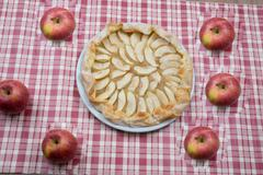 Arrangement of home-made apple pie and apples. Stock Photos