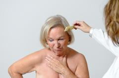 Elderly lady gets her hair combed - stock photo