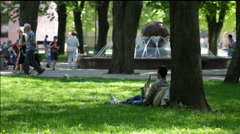 A young man plays the saxophone sitting under tree in the park Stock Footage
