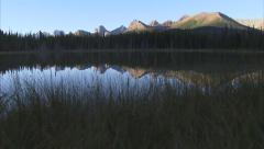 Mountain reflections in an alpine lake dolly shot Stock Footage