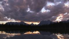 Alpine Lake sunset reflection tilt down from clouds Stock Footage