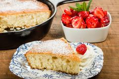 Slice of skillet cake with cream and berry - stock photo