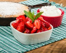 Bowl of glazed strawberries with skillet cake Stock Photos