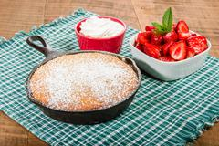 Cast iron skillet with cake and berries - stock photo