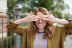 Cheerful Teen Girl Covering her Eyes with Hands - stock photo