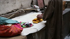 Man arranging ironed piece of clothing at street in Varanasi. Stock Footage