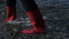 4K woman in red boots are walking in the water at the shoreline on pebble beach Stock Footage