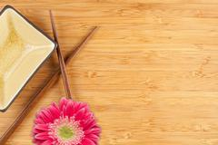 Stock Photo of Gerber Daisy, Chopsticks and Dish on a Bamboo Background with Copy Space.