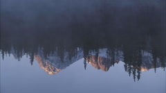 Mountain and forest reflections in alpine lake Stock Footage
