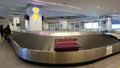 Transporter at arrival hall, luggage reclaim area, woman took case Stock Footage