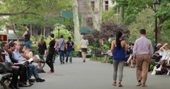 People sitting on benches walking in a city park Stock Footage
