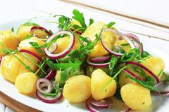 Potatoes with arugula and Spanish onion Stock Photos