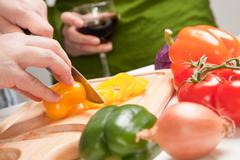 Man Slicing Vegetables on Cutting Board While Woman Enjoys a Glass of Red Win Stock Photos