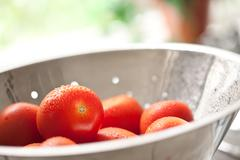 Macro of Fresh, Vibrant Roma Tomatoes in Colander with Water Drops Abstract. - stock photo