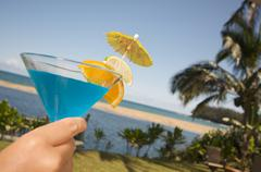 Woman with Tropical Drinks on Lanai - stock photo