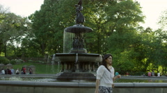 Girl Walking in front Central Park Bethesda Fountain Statue Slow Motion 4K NYC - stock footage