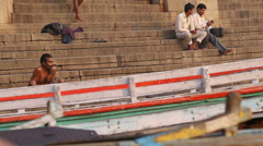 Men sitting at ghat of Ganges river in Varanasi, with boats in front. Stock Footage
