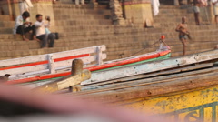 Closeup of boats at Varanasi dock, with people at ghat in background. Stock Footage