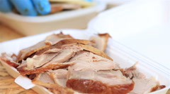 Street vendor packs the pieces of Peking duck in the lunchbox. Close up. Stock Footage