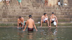 Group of men bathing and sitting at ghat of Ganges river in Varanasi. Stock Footage