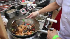 Street cook prepares Chinese noodles with vegetables in a city park. Stock Footage