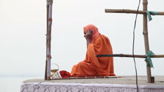 Man in traditional clothing sitting at street in Varanasi and talking on phone. Stock Footage