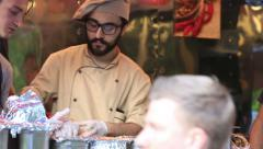 Street chefs prepare and sell fast hot meals to passers-by. - stock footage