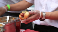 Street vendors prepares classic hot dog with vegetables. - stock footage