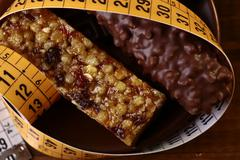 Tasty chocolate bars and peanut brittle with a measuring tape - stock photo