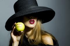 Tempting blonde girl with apple - stock photo