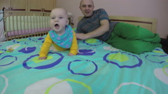 Father man help his baby daughter turn over on bed at home. 4K Stock Footage