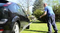 Worker man wash car automobile with water jet on lawn in summer Stock Footage