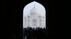 Taj Mahal facade view from dark indoors, with people in front. Stock Footage