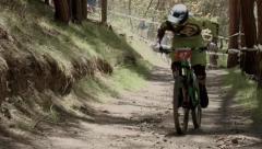 Three Mountain bikers racing downhill through tree's, Scotland Stock Footage