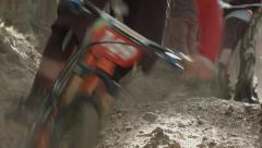 Mountain bikers racing downhill through tree's, Scotland Stock Footage
