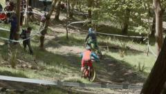 Mountain bikers racing downhill through tree's, Scotland Stock Footage