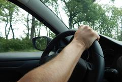 Mans hand on steering wheel in car at speed - stock photo