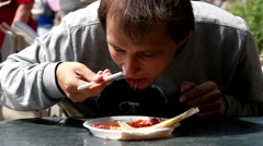 Street Food Festival - man eating outdoors a break for lunch Stock Footage