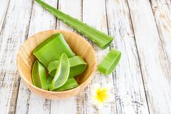 Aloe Vera leaves in wooden bowl on wooden table Stock Photos