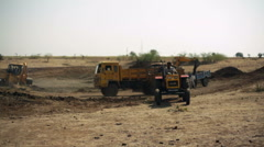 Bulldozer and trucks doing earthworks in India, long shot, shallow DOF Stock Footage