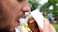 Young bearded man greedily eating fresh tasty hamburger outdoors lunch break  Stock Footage