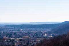 Escarpment and hills receding into hazy white distance. - stock photo
