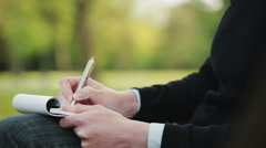Woman Taking Notes in a Park Stock Footage