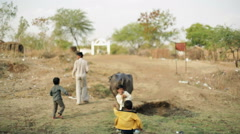 Man with buffalo and dancing happy kids, India, shallow DOF Stock Footage