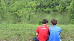 Two friends Talking on the bank of forest lake with tablet computer Stock Footage