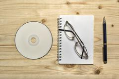 Blank stationery set : glasses, CD, notebook, and penci - stock photo