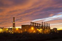 A steel plant under a fiery red evening sky. Stock Photos