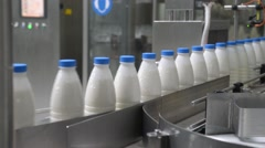 Stock Video Footage of Milk bottles move along the conveyor in the apparatus of pouring milk