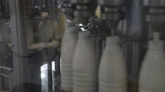 Milk bottles move along the conveyor in the apparatus of pouring milk Stock Footage