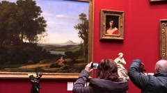 At the art gallery. Visitors observe and photographing paintings smartphones Stock Footage